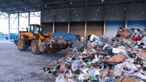Экскаватор-погрузчик на территории комплекса по переработке отходов