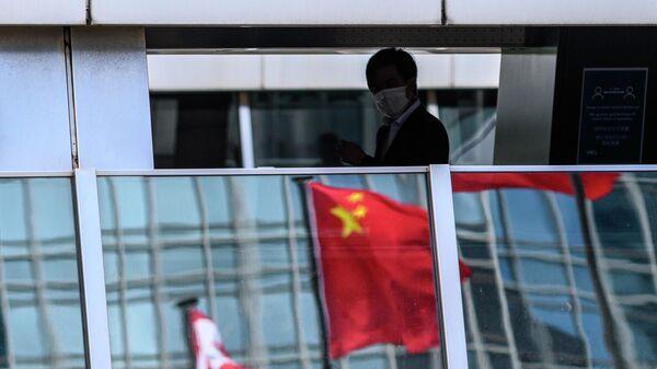 Мужчина на пешеходном мосту, в котором отражается флаг Китая, Гонконг