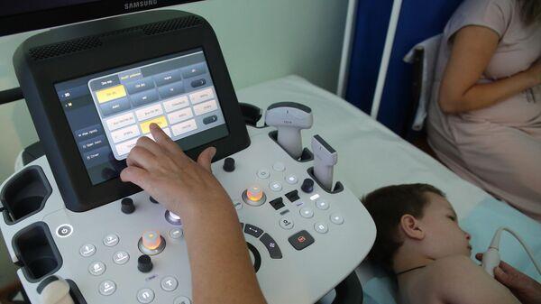 Специалист проводит ультразвуковое исследование (УЗИ) ребёнку