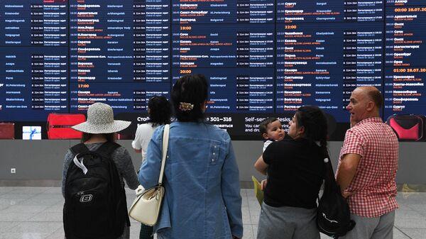 Пассажиры у электронного табло в терминале B аэропорта Шереметьево