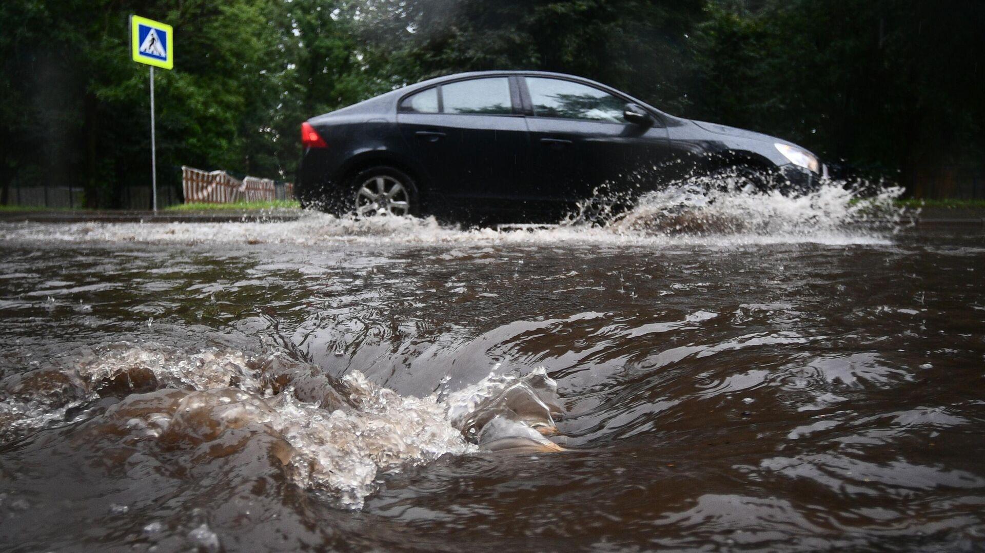 Автомобиль едет по подтопленной из-за дождя дороге в Москве - РИА Новости, 1920, 18.09.2020