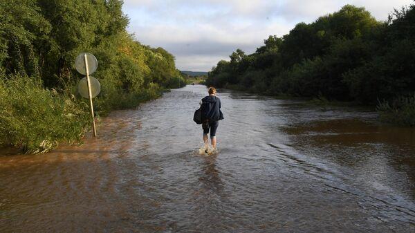 Женщина идет по затопленной паводком дороге
