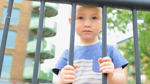 Мальчик стоит возле забора