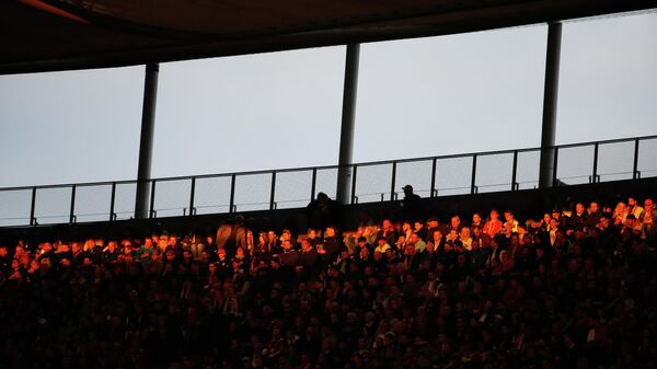 A stripe of the setting sun shines on the fans during the German Cup (DFB Pokal) Final football match RB Leipzig v FC Bayern Munich at the Olympic Stadium in Berlin on May 25, 2019. (Photo by Odd ANDERSEN / AFP) / DFB REGULATIONS PROHIBIT ANY USE OF PHOTOGRAPHS AS IMAGE SEQUENCES AND QUASI-VIDEO.