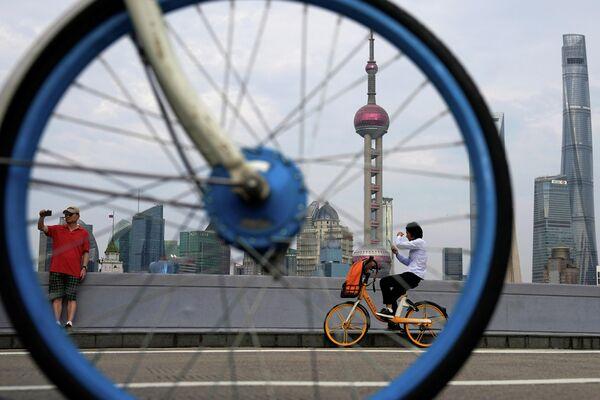 Люди катаются на велосипедах около финансового района Луцзяцзуй в Шанхае