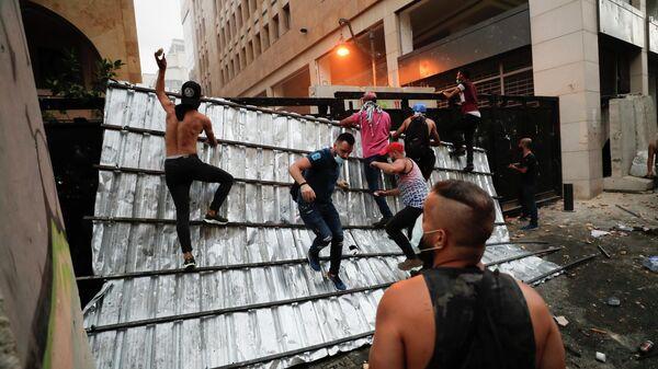 Люди преодолевают полицейский барьер во время протеста в Бейруте, Ливан. 9 августа 2020