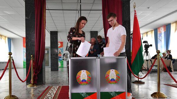 Молодые люди голосуют на выборах президента Белоруссии на избирательном участке в Минске