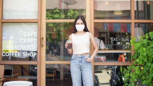 Девушка в защитной маске выходит из кафе
