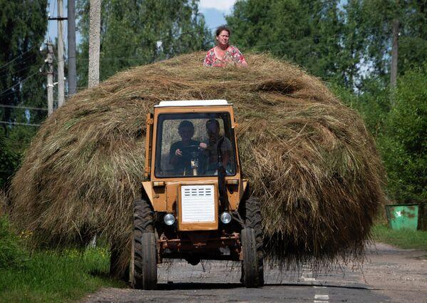 Женщина сидит на куче сена, которую везет трактор, в деревне Сера, Россия