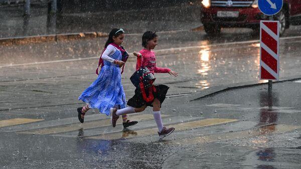 Девочки перебегают через дорогу во время сильного дождя в Москве