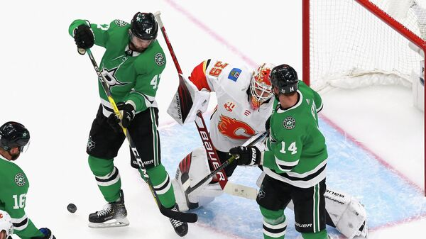 EDMONTON, ALBERTA - AUGUST 13: Cam Talbot #39 of the Calgary Flames defends the net against Alexander Radulov #47 and Jamie Benn #14 of the Dallas Stars in Game Two of the Western Conference First Round during the 2020 NHL Stanley Cup Playoffs at Rogers Place on August 13, 2020 in Edmonton, Alberta, Canada.   Jeff Vinnick/Getty Images/AFP