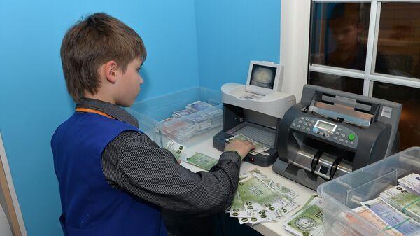 Мальчик проверяет подлинность банкнот на специальной аппаратуре в Детском банке