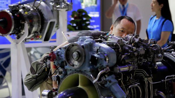 Мужчина рассматривает двигатель вертолета, разработанный компанией Мотор Сич, представленный на выставке Aviation Expo China в Пекине