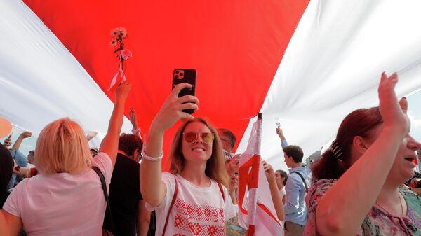 Демонстранты держат гигантский бело-красно-белый флаг Беларуси во время акции протеста против результатов президентских выборов в Минске, Беларусь