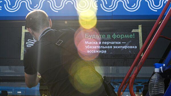 Размещение наклейки на электробусе, напоминающей о необходимости носить маски и перчатки в транспорте Москвы