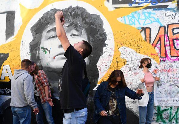 Поклонники Виктора Цоя собрались у его стены на Арбате, чтобы почтить память музыканта в тридцатую годовщину его гибели