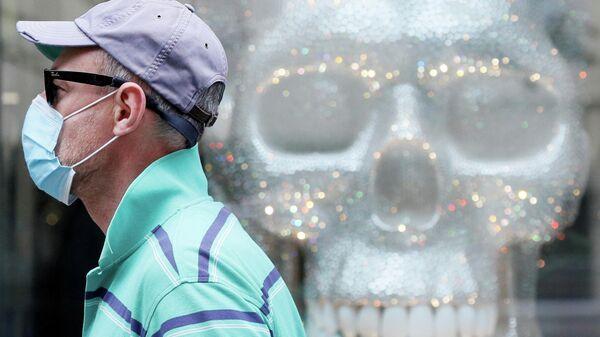Мужчина в защитной маске проходит мимо витрины магазина в Киеве