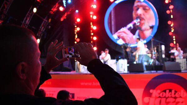 Зритель фотографирует выступление музыкантов на открытии Международного музыкального фестиваля Koktebel Jazz Party в Крыму