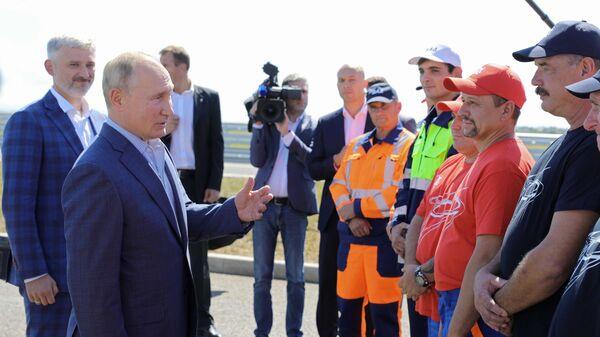 Президент РФ Владимир Путин беседует с дорожниками, которые принимали участие в строительстве, на церемонии запуска движения по трассе Таврида в Крыму
