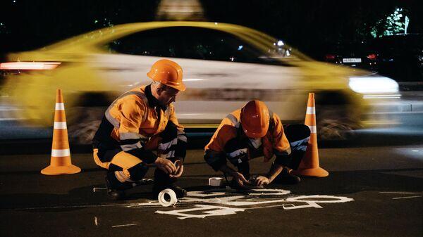 Специалисты комплекса городского хозяйства наносят на дорогу в преддверии знак Осторожно, дети!