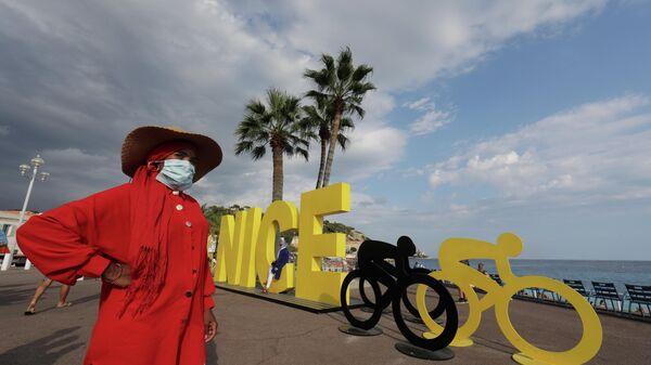 Жещина в защитной маске на Английской набережной в Ницце