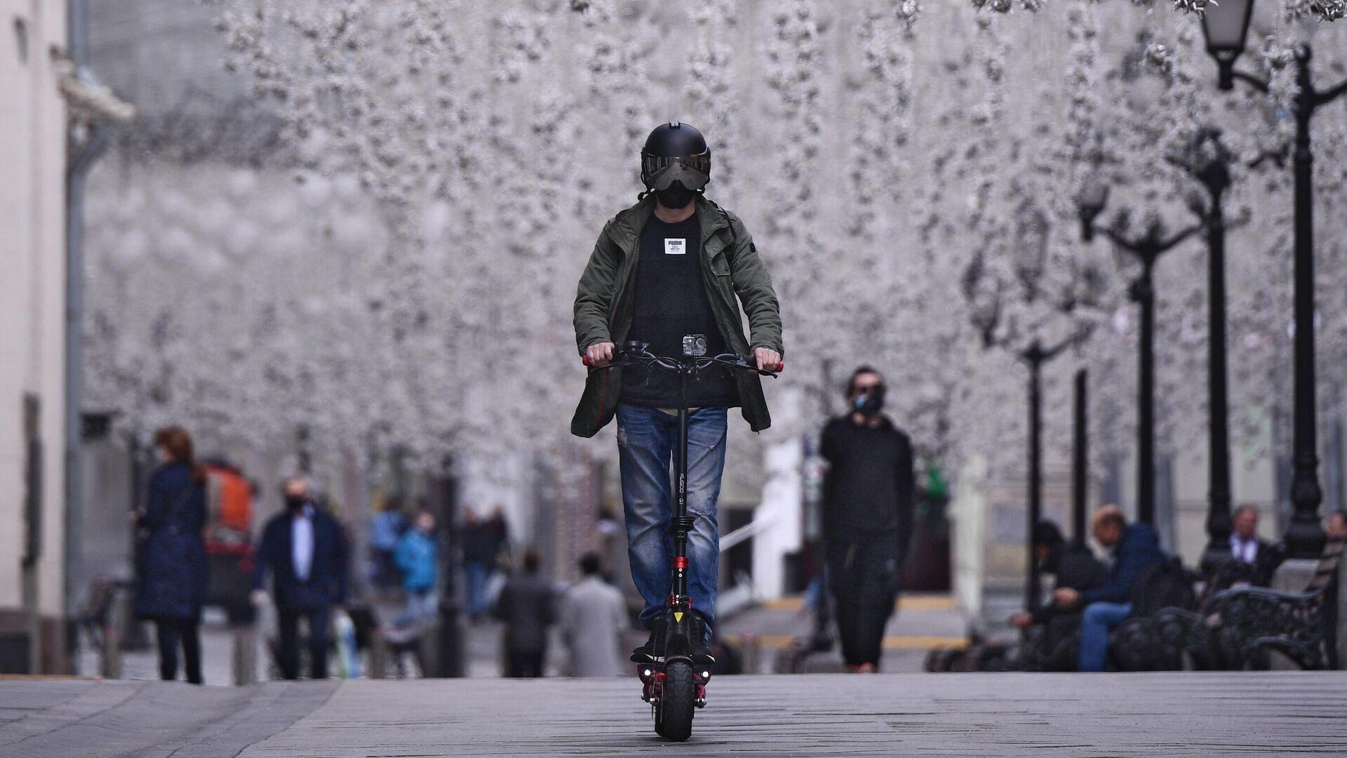 Мужчина в защитном шлеме катается на электросамокате - РИА Новости, 1920, 07.04.2021