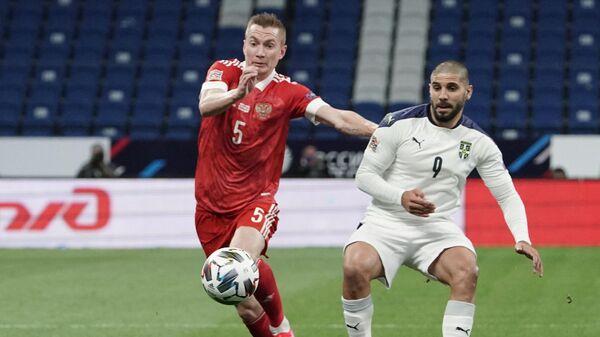 Защитник сборной России Андрей Семенов (слева) и нападающий сборной Сербии Александар Митрович
