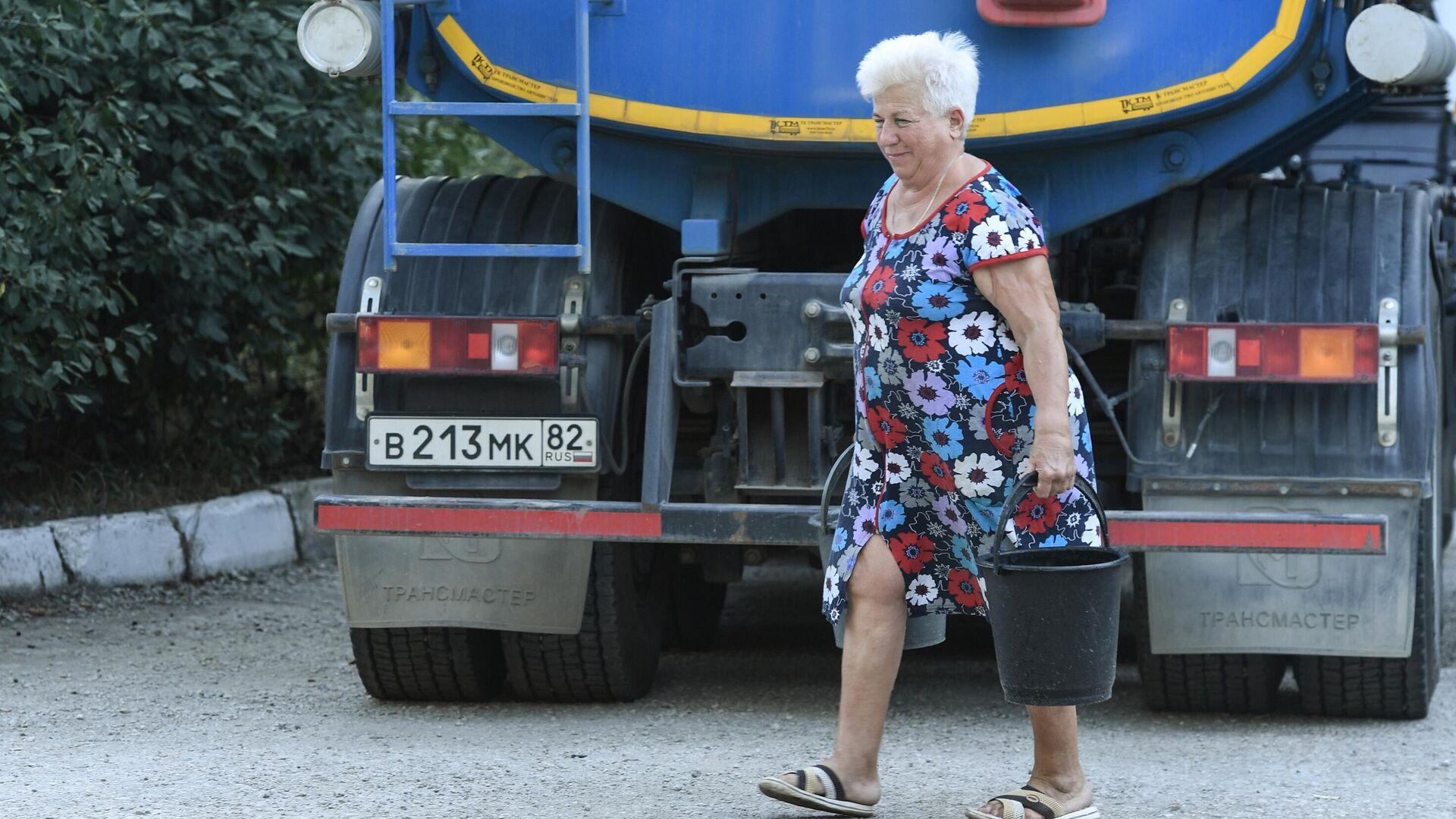 Жительница Cимферополя с набранной в ведра питьевой водой, привезенной в цистернах - РИА Новости, 1920, 08.09.2020