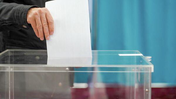 Мужчина опускает бюллетень в урну для голосования