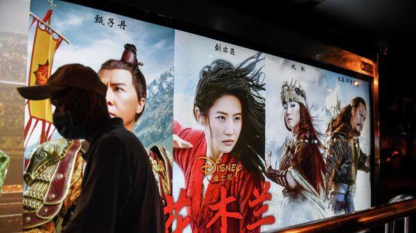 Мужчина проходит мимо плаката фильма Мулан студии Disney на автобусной остановке в Пекине