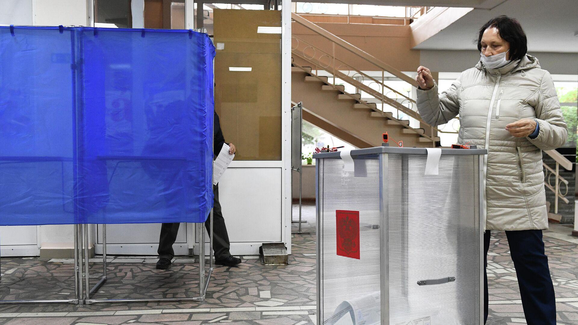 Женщина голосует на выборах губернатора Иркутской области на избирательном участке в Иркутске - РИА Новости, 1920, 13.09.2020