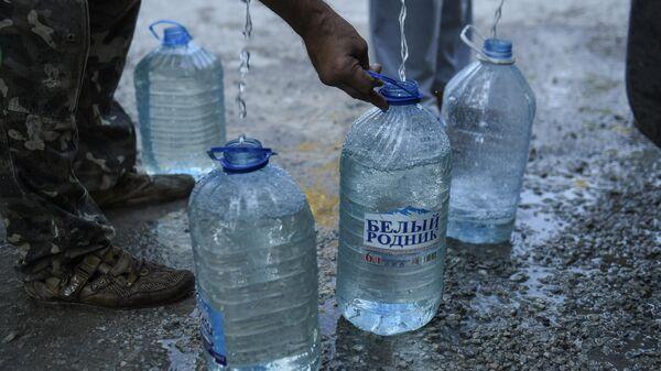 Жители Cимферополя набирают в емкости питьевую воду, привезенную в цистерна