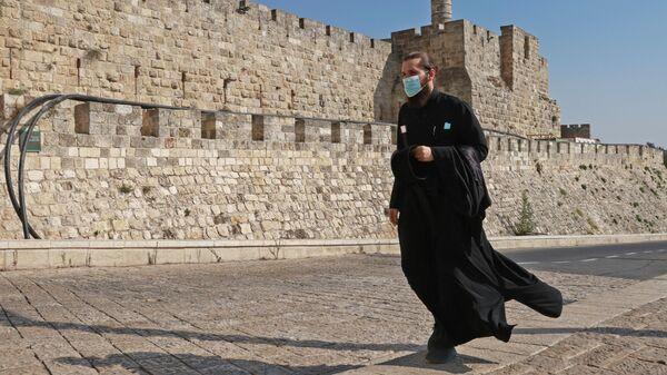 Священнослужитель в защитной маске в Старом городе Иерусалима