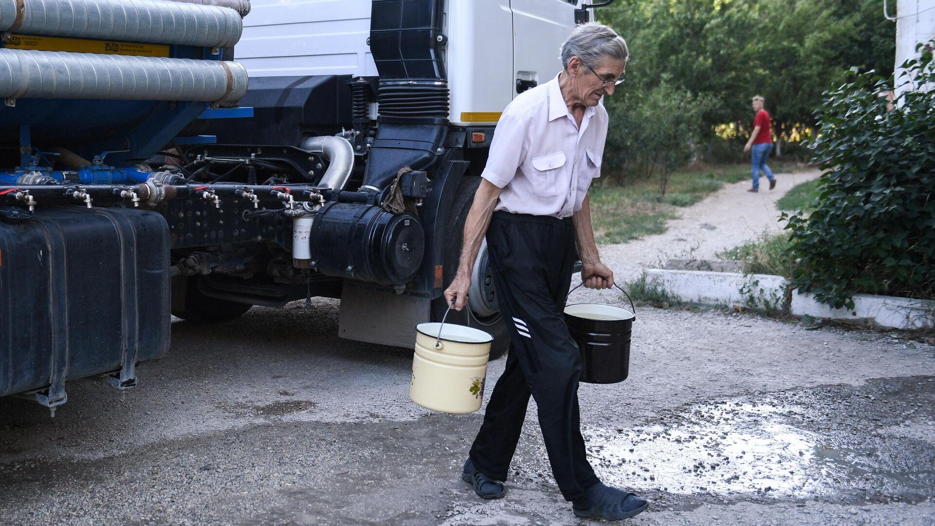 Житель Cимферополя набирает в емкости питьевую воду, привезенную в цистернах - РИА Новости, 1920, 22.11.2020