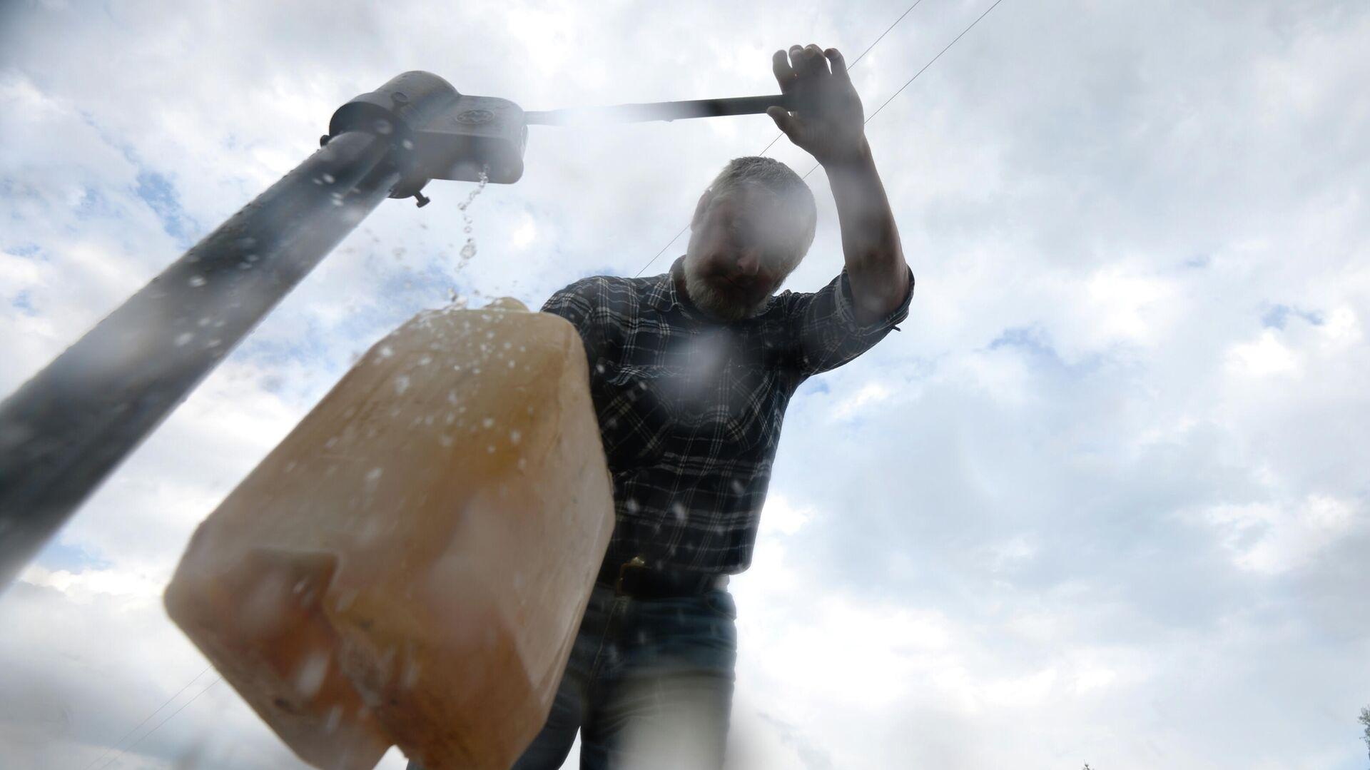 Мужчина набирает воду из колонки - РИА Новости, 1920, 23.03.2021