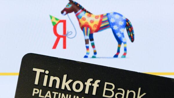 Платиновая карта банка Тинькофф и логотип компании Яндекс