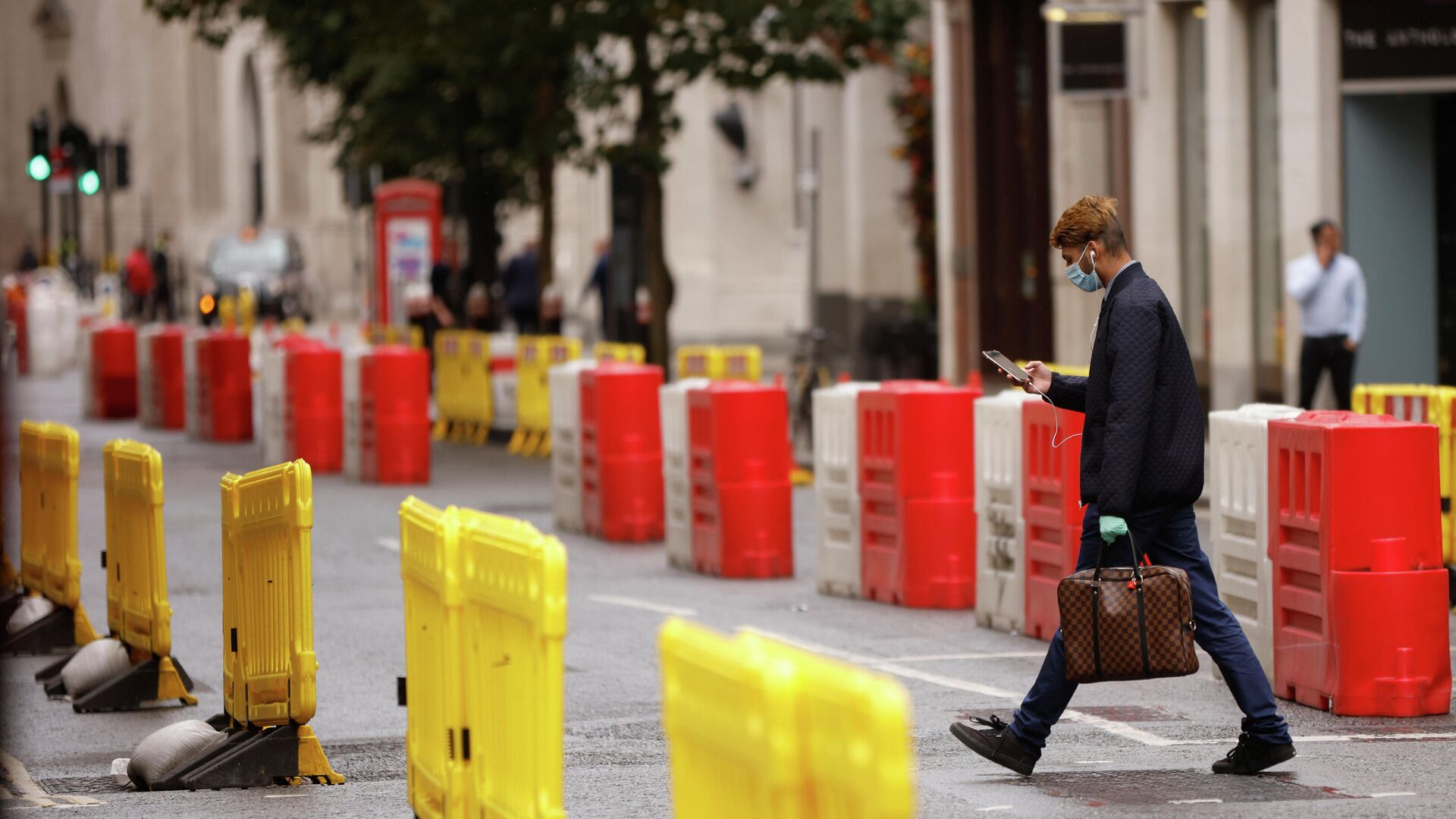 Мужчина в защитной маске переходит дорогу с установленными на ней барьерами для социального дистанцирования в Лондоне - РИА Новости, 1920, 24.09.2020