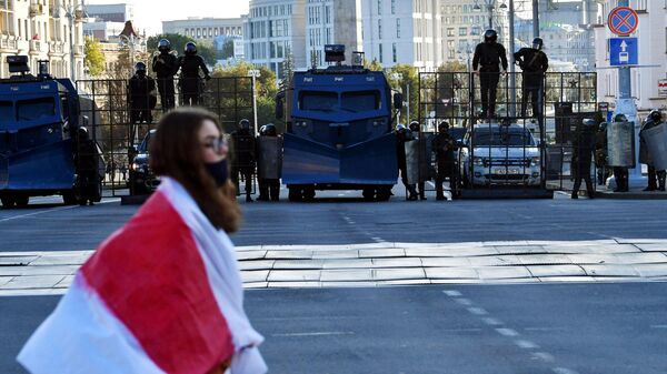 Участница и сотрудники правоохранительных органов во время акции протеста Марш справедливости в Минске