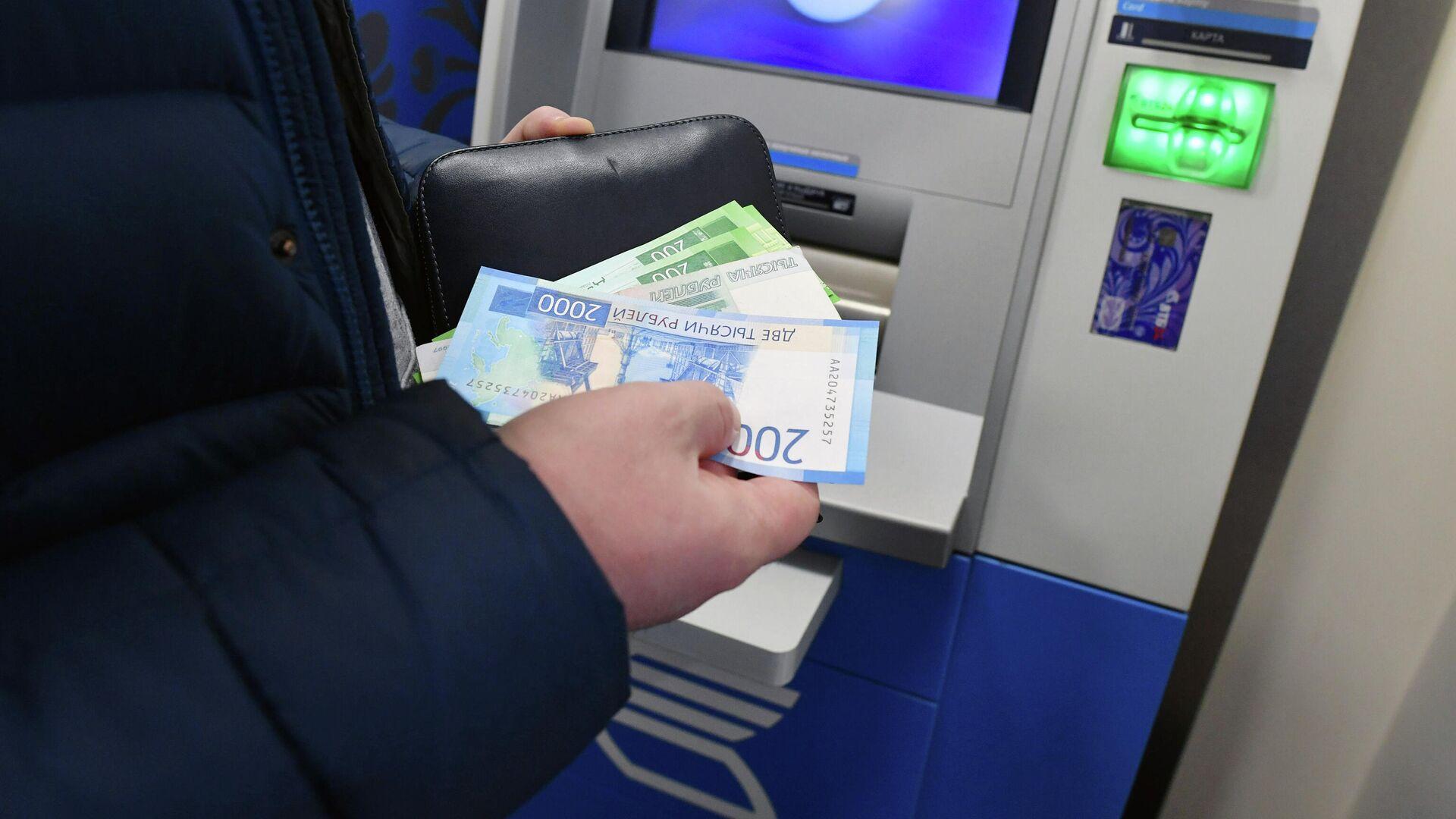 Женщина производит снятие денег в банкомате - РИА Новости, 1920, 21.10.2020