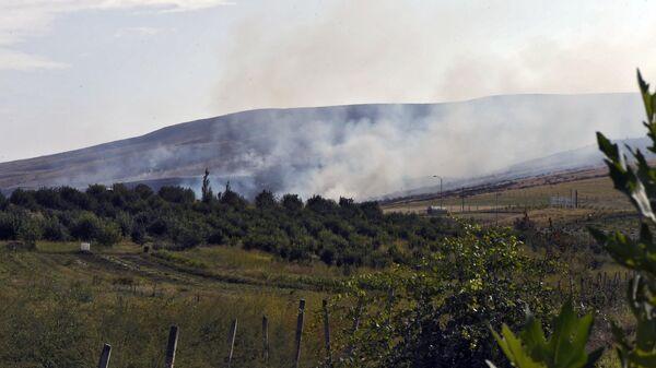 Дым от пожара, возникшего в результате обстрела в Мартакертском районе Нагорного Карабаха
