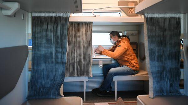 Мужчина в павильоне с макетом нового плацкартного вагона для поездов дальнего следования