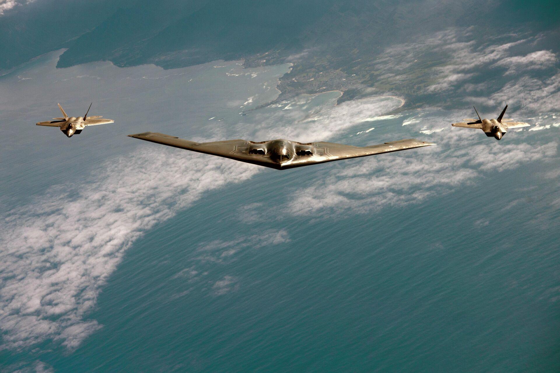 Американский малозаметный стратегический бомбардировщик Northrop B-2 Spirit в сопровождении истребителей F-22 Raptor - РИА Новости, 1920, 01.03.2021