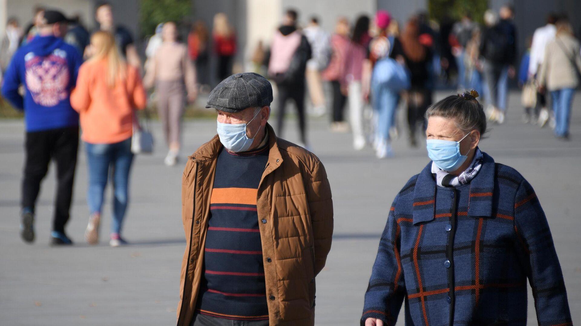 Люди в медицинских масках на территории парка ВДНХ в Москве - РИА Новости, 1920, 05.10.2020