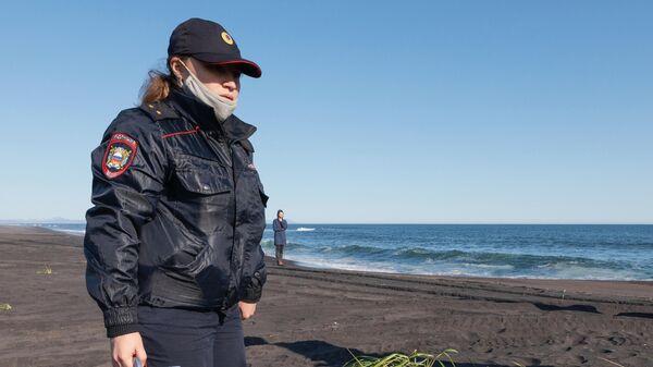 Сотрудник УМВД Камчатского края во время оперативно-разыскных мероприятий на месте предполагаемого происшествия на Халактырском пляже на Камчатке