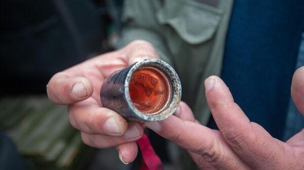 Мужчина держит в руке кассетный (кластерный) боеприпас, найденный после ночных обстрелов Степанакерта