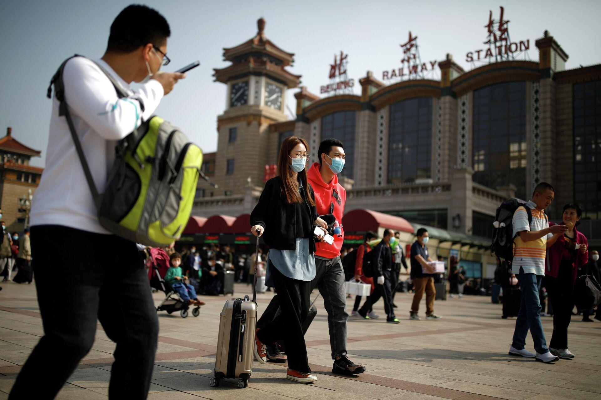 Люди с защитных масках возле железнодорожного вокзала в Пекине  - РИА Новости, 1920, 07.10.2020