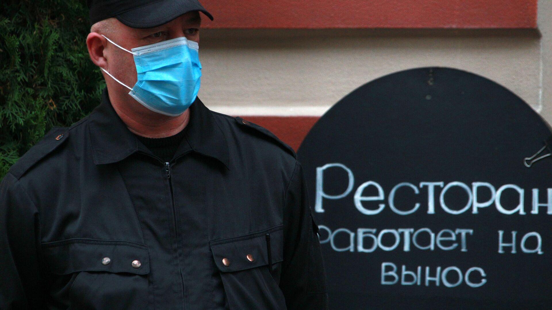 Сотрудник охраны в медицинской маске на улице Арбат в Москве - РИА Новости, 1920, 27.10.2020