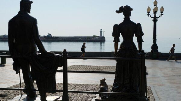 Отдыхающие у скульптуры героев рассказа А.П. Чехова Дама с собачкой на набережной Ялты