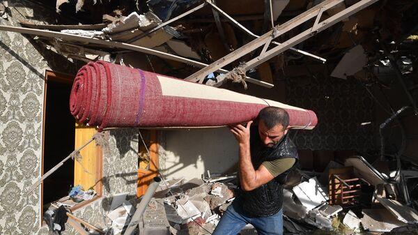 Жители с уцелевшим ковром вещи на развалинах своего жилого дома, разрушенного в результате ракетного обстрела города Гянджа
