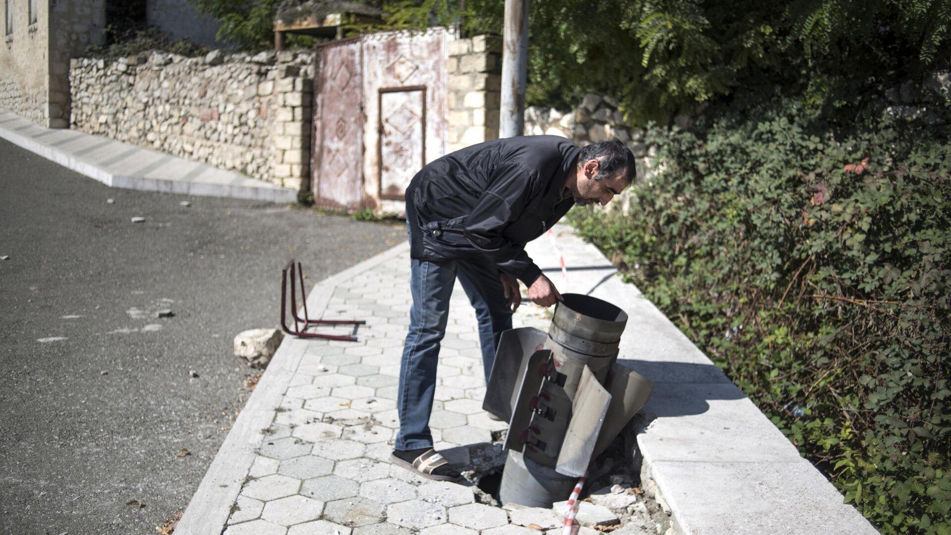 Местный житель у не разорвавшегося снаряда на улице города Мартуни - РИА Новости, 1920, 16.10.2020